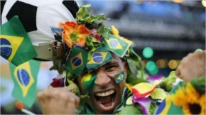 A Brazil soccer fan covered in flowers and his nation's flag cheers inside the FIFA Fan fest area before the start of the World Cup soccer game between Brazil and Croatia