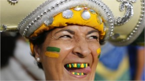 A Brazil soccer fan with her teeth decorated in the colors of her soccer team poses for a photo before watching the world cup semi final
