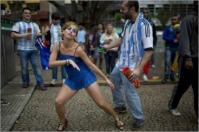 A Brazilian national soccer fan, left center, dances with an Argentine fan  as they wait for the start of the live telecast of the world cup