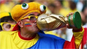 A Colombia fan kisses a replica of the World Cup trophy during the 2014 FIFA World Cup Brazil Quarter Final match between Brazil and Colombia at Castelao