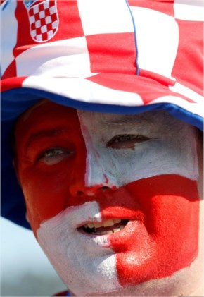 A Croatian fan with his face painted in the Croatian national soccer team's colors waits to enter Itaquerao Stadium to watch the World Cup opening match, Brazil