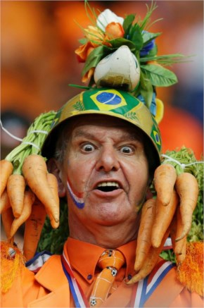 A Dutch fan wears a helmet with a Brazilian flag motif, decorated with carrots hanging from its sides.