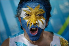 A fan cheers for Argentina with his face painted to represent his country's national flag
