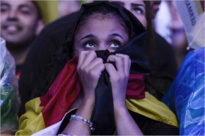 A fan covered in a German flag watches the the FIFA World Cup 2014