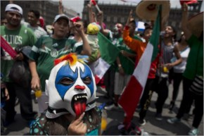 A masked girl poses for photo surrounded by Mexico soccer fans as they watch their team's World Cup