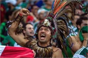 A Mexico fan dressed up in a costume celebrates a goal during the 2014 FIFA World Cup Brazil