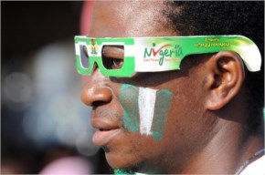 A Nigeria fan with his face painted in the colors of the country's green and white flag watches the 2014 FIFA World Cup