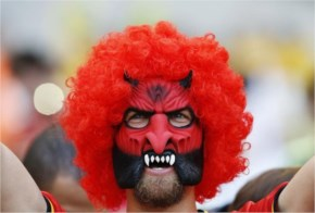 A Spanish soccer fan covers her face as she watches on a giant display a World Cup soccer match between Spain and Chile