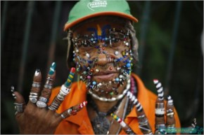 A street cleaner and fan of the Brazilian national World Cup soccer team shows the myriad of piercings on her face, and her silver rings