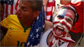 A U.S. supporter and a Brazil supporter celebrate the United States advancing to Round 16 after their loss to Germany while watching the match at FIFA Fan Fest.