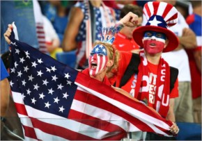 A United States fan cheers while holding an American flag prior to the 2014 FIFA World Cup Brazil