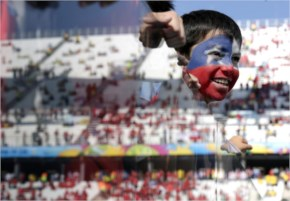 A young Chilean fan looks out onto the pitch before the group B World Cup soccer match between the Netherlands and Chile