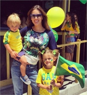 Alessandra Ambrosio photograph with her daughter and son, clad in Brazil's team colours.
