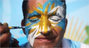 An Argentina fan has his face painted before the start of the Argentina match outside FIFA Fan Fest