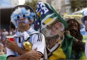 An Argentina football fan watches his team's World Cup match with Iran as another fan holds up a photo of Pope Francis inside the FIFA Fan 2014