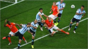 Ezequiel Garay of Argentina and Ron Vlaar of the Netherlands compete for the ball on a Netherlands cross during the 2014 FIFA World Cup Brazil