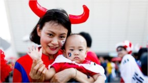 Fans of Korea, including a woman in her horns and her baby, arrive at Arena de Sao Paulo to watch the match between Korea Republic and Belgium for the 2014 FIFA World Cup.