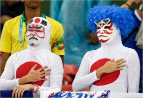 Japanese fans listen to their nation's national anthem before the Group C World Cup soccer match between Ivory Coast and Japan at the Arena Pernambuco in Recife, Brazil