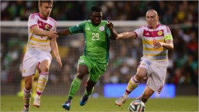 Michael Babatunde of Nigeria battles with James Morrison and Scott Brown of Scotland