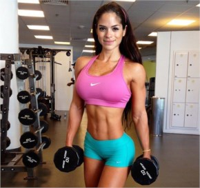 Michelle Lewin working out in the gym with dumbbells
