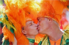 Netherlands fans in colorful getups kiss during the 2014 FIFA World Cup Brazil