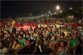 People watch on a huge screen the Brazil vs Croatia opening match during the FIFA Fan Fest in Copacabana Beach in Rio de Janeiro, Brazil