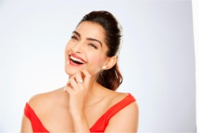 Sonam Kapoor Reddish Dress Face with a Cute Smile and a pony-tail hairstyle