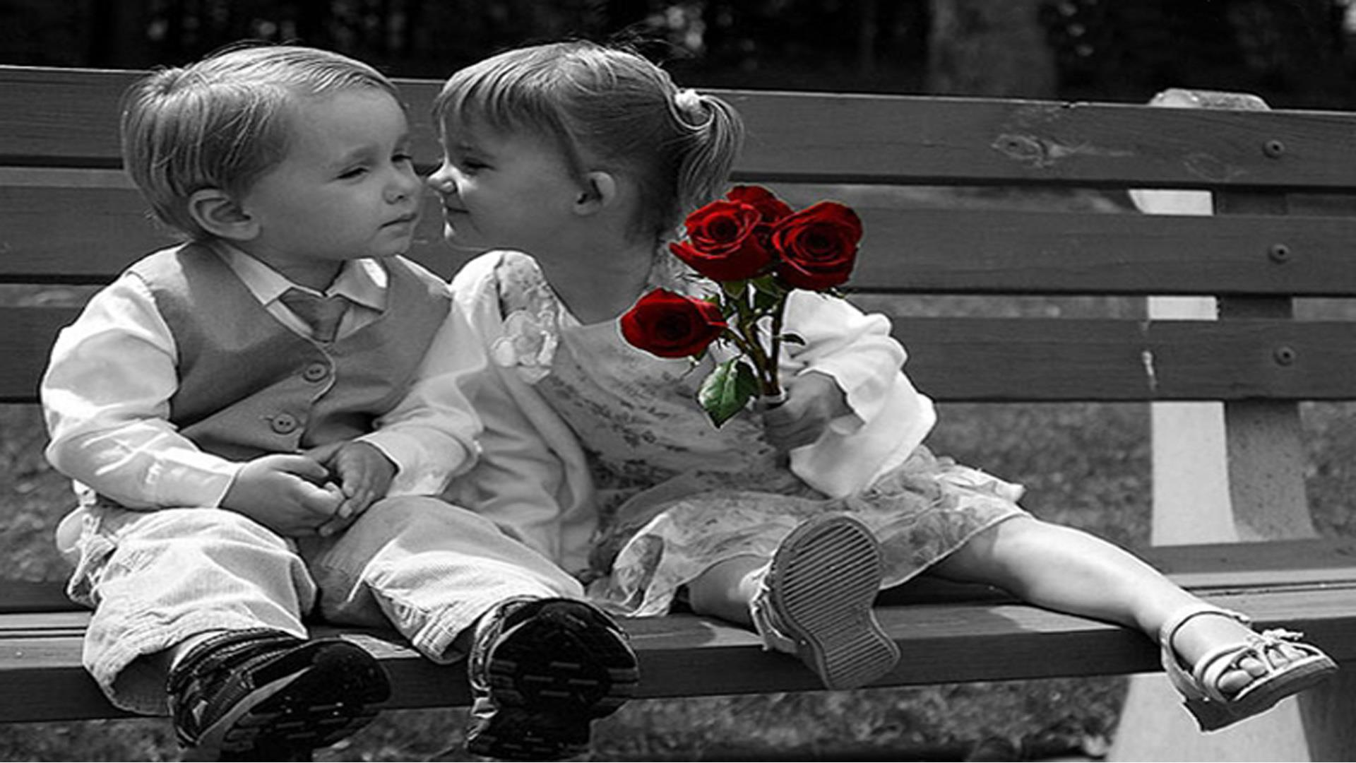 cute babies - little boy and girl kissing in hand red roses